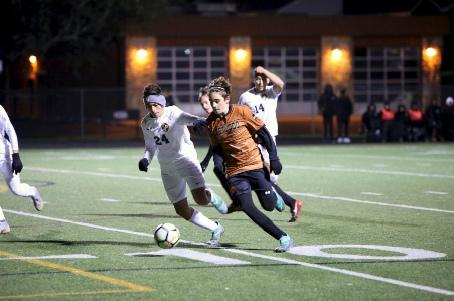 Niko Djordjevic '21 kicks the ball across the field with an opponent close behind.