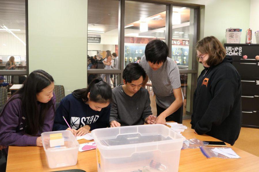 Ashlynn Arcaya '20 looks on as seniors Ethan Lao and Anthony Pham determinedly work on a puzzle.