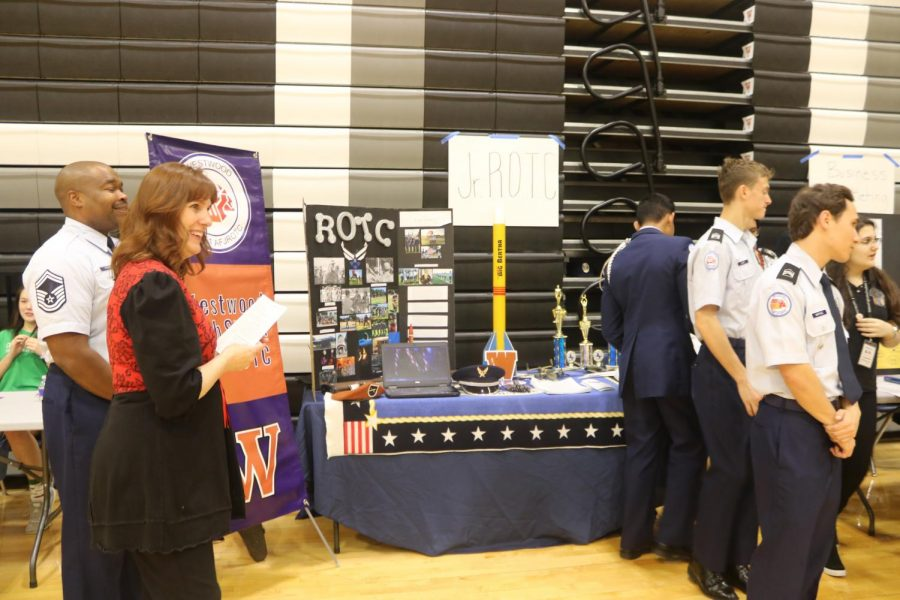 ROTC students and teachers cheerfully await the arrival of the eighth graders, ready to answer their inquiries about the program.