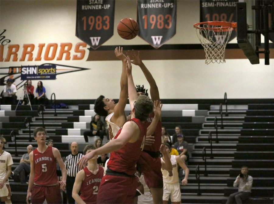 Christian Robinson 20 shoots against two Leander defenders.