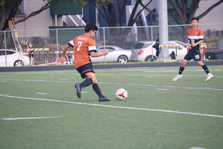 Emanuel Molina '21 kicks the ball across the field.