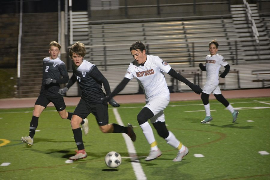 Theo Givens 20 attempts to outrun Vandegrift defenders with Niko Djordjevic 21 trailing behind.