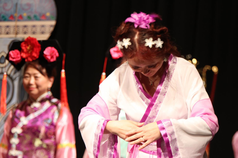 A+performer+bows+down+while+representing+a+fashion+era+of+China.