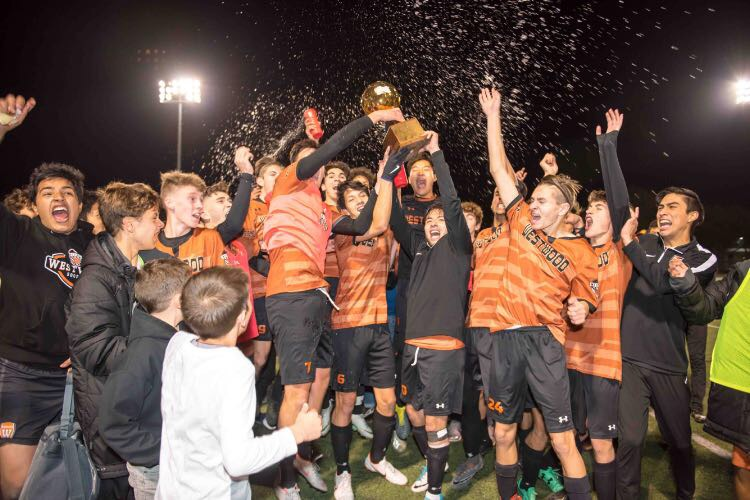 In an uproarious celebration, the varsity boys' celebrate with the District Championship trophy. Photo Courtesy of Xiaowei Wang.