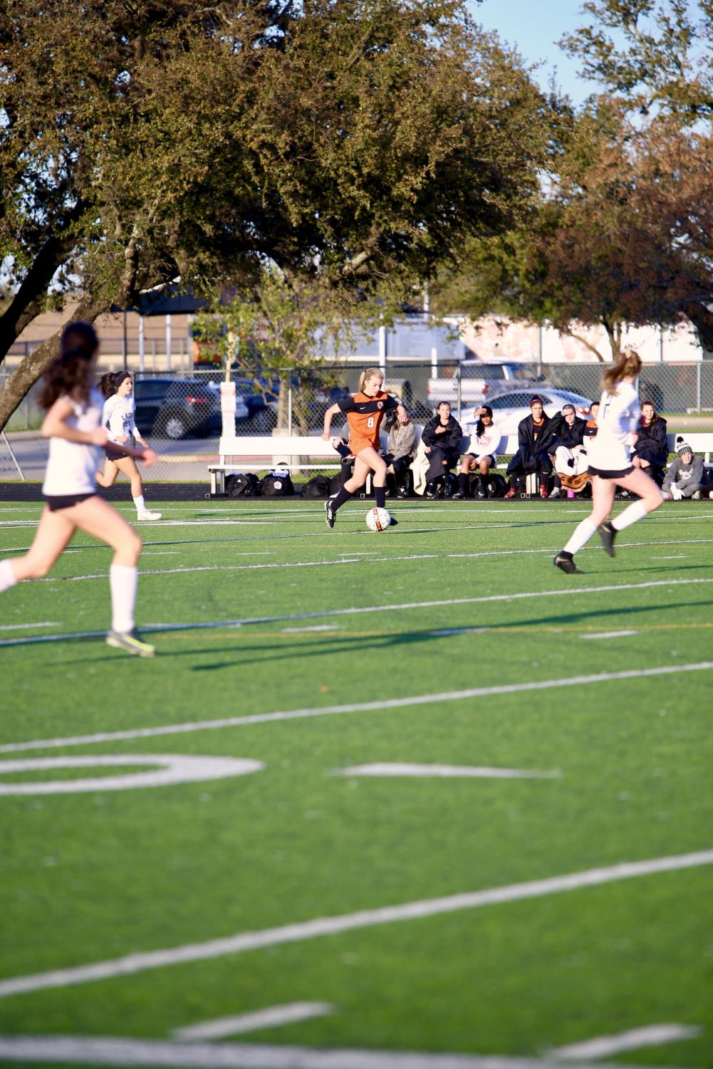 Katelyn+Woodruff+%2721+dribbles+the+ball+downfield%2C+surrounded+by+opponents.