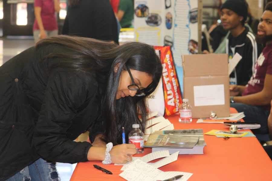 Sweni Karedia '22 writing a thank you note at the Academy Ambassador booth for the organizations that visited.
