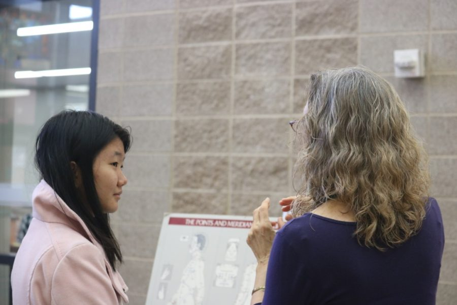Denise Lin '21 learns from a professional at a health science booth.