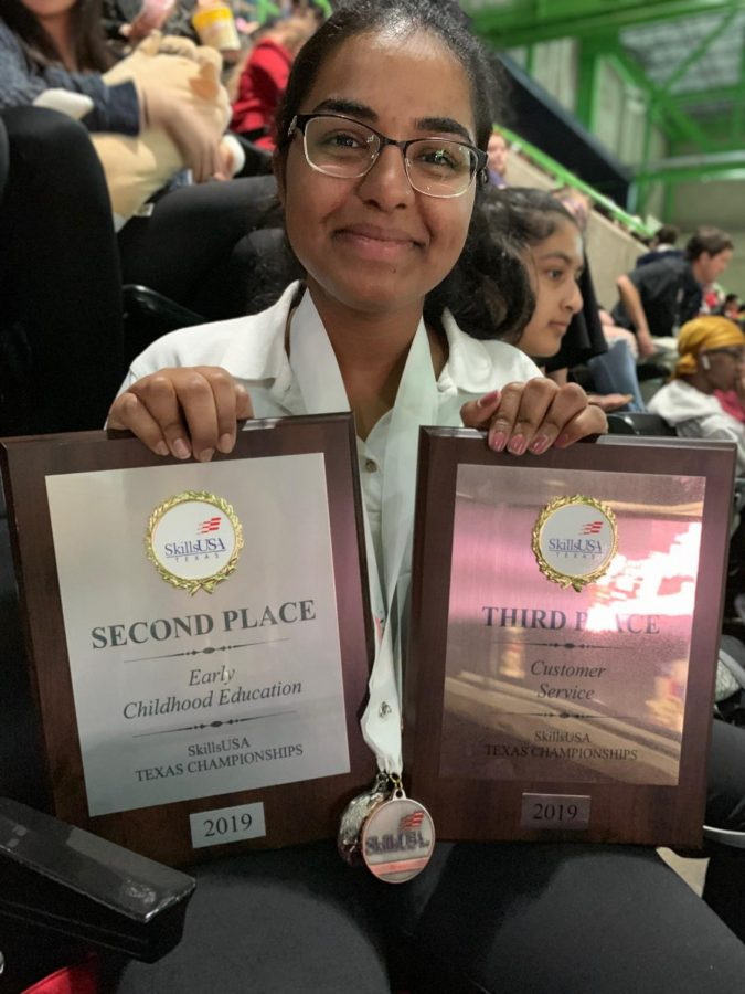 Anuja Uppuluri '21 holds up her awards after the closing ceremony.