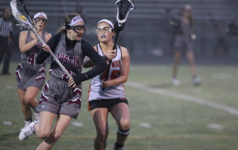 Stephanie Shih '20 eyes the ball in the opponent's lacrosse stick.