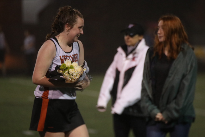Grace+Healy+%2719+walks+towards+the+bleachers+with+a+bouquet+in+her+hands.+