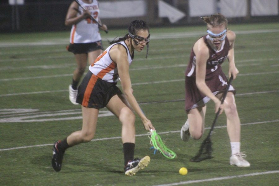 Riya Shah '20 and an Austin Maroon player simultaneously attempt to pick up the ground ball.