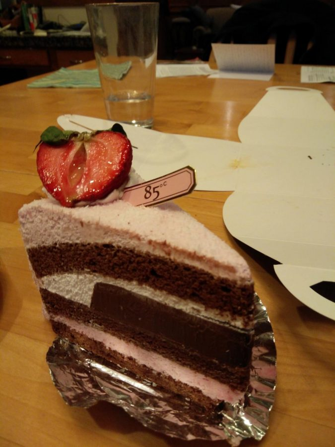 The rich Strawberry Chocolate Mousse cake is a soft pink color with a strawberry decorating the top.