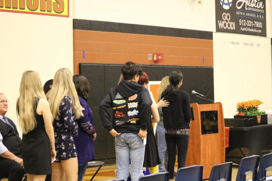 Students stand in a line before their names are announced.