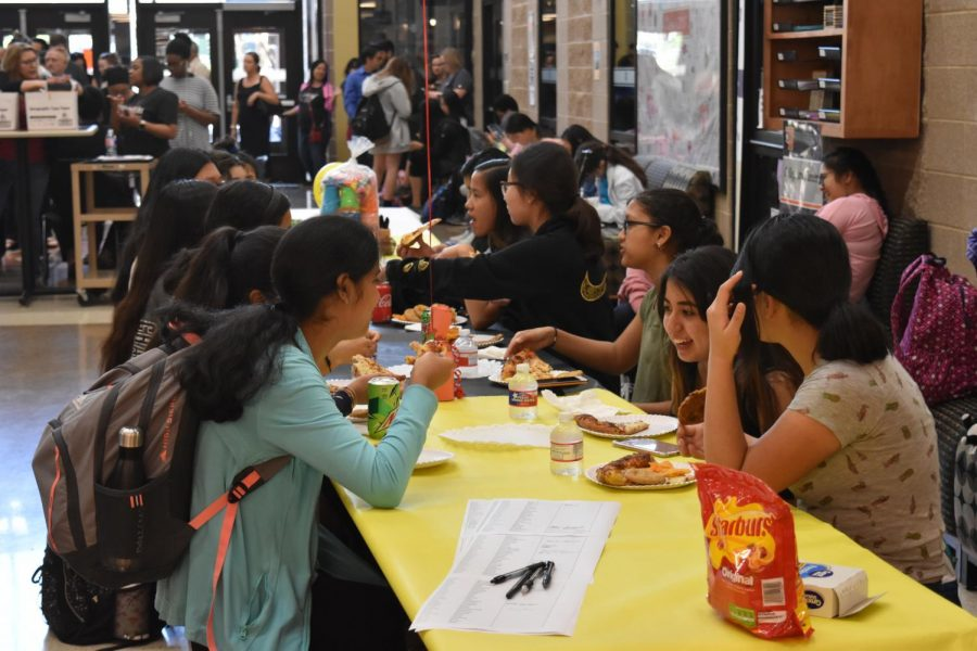Students eat and chat with each other.
