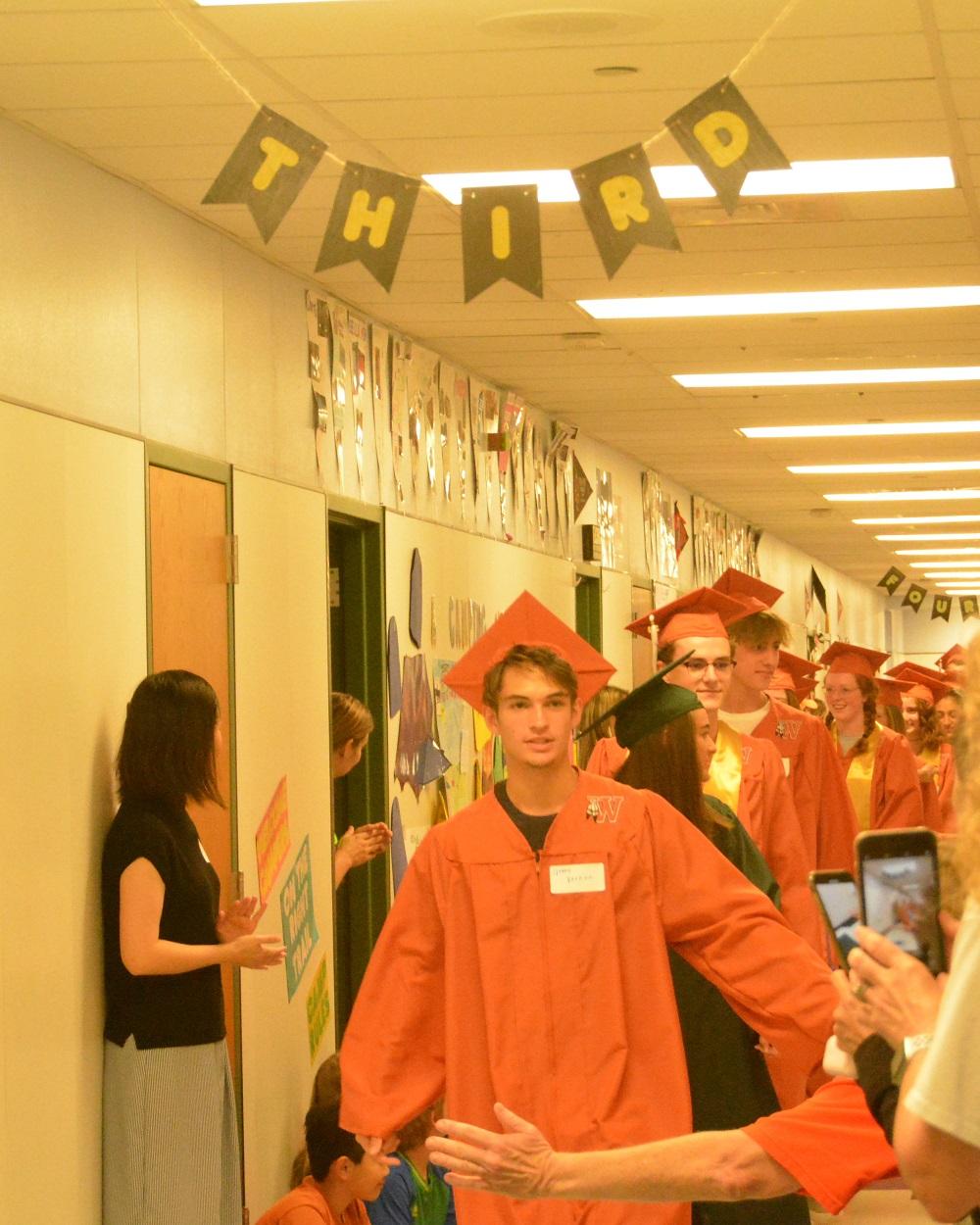 Seniors+walk+down+a+hallway+as+parents%2C+students%2C+and+teachers+congratulate+them.