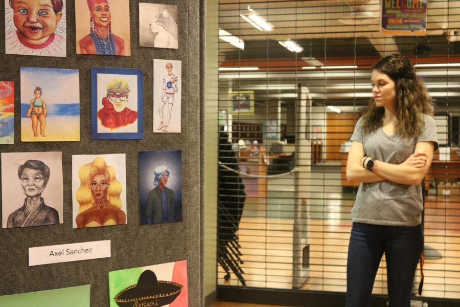 Ms. Katherine Hickman observes the art at the Senior Art Show.