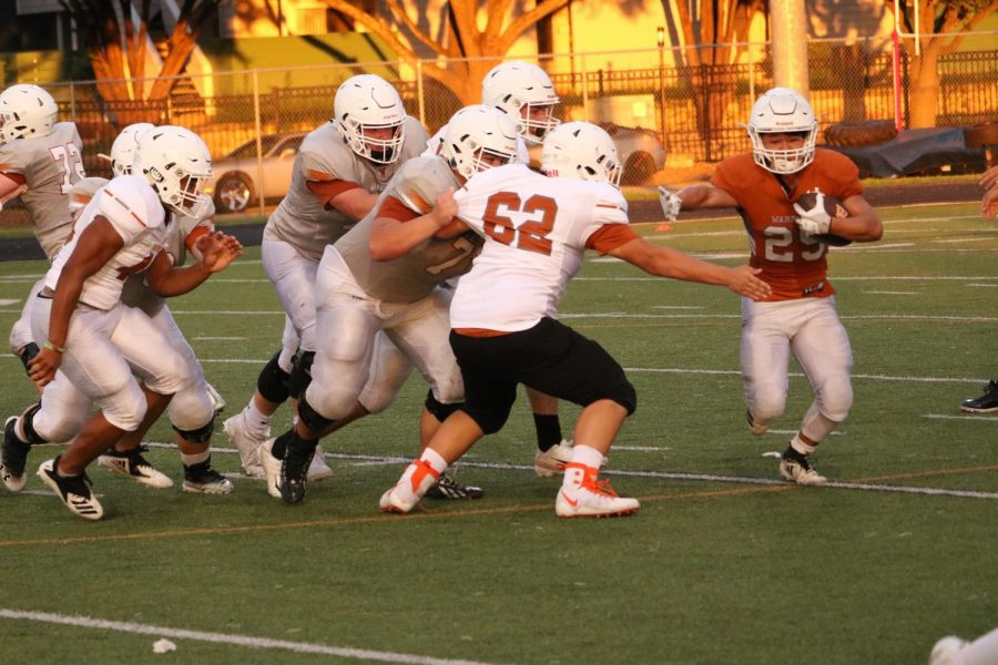 Brian Lee 22 extends a stiff arm as he tries to escape the reach of Malachi Jacobs 22.