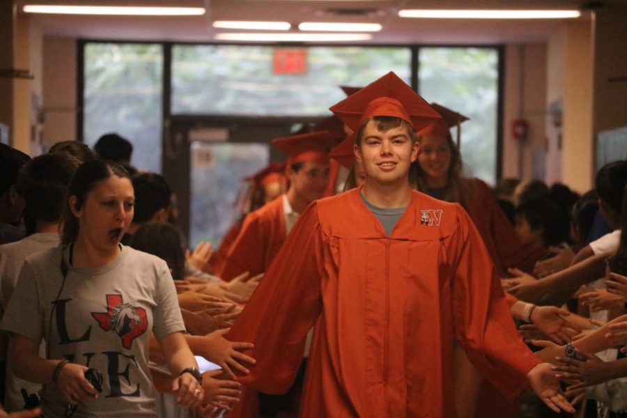 Luke Durham 19 high-fives the students while entering Canyon Vista.
