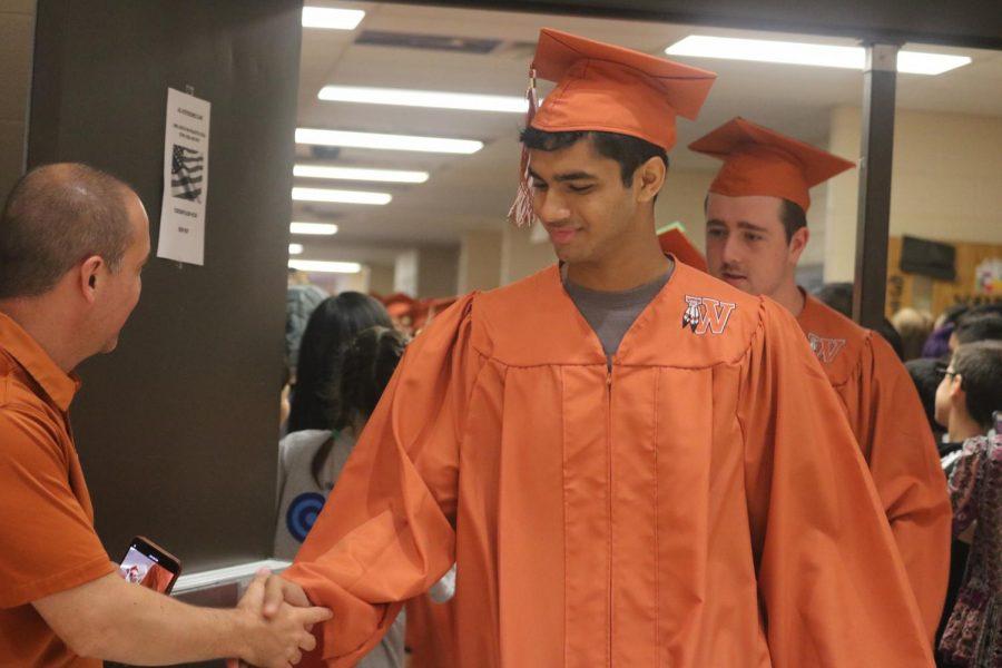 Harsha Jandhyala '19 shakes hands with Principal Mario Acosta.