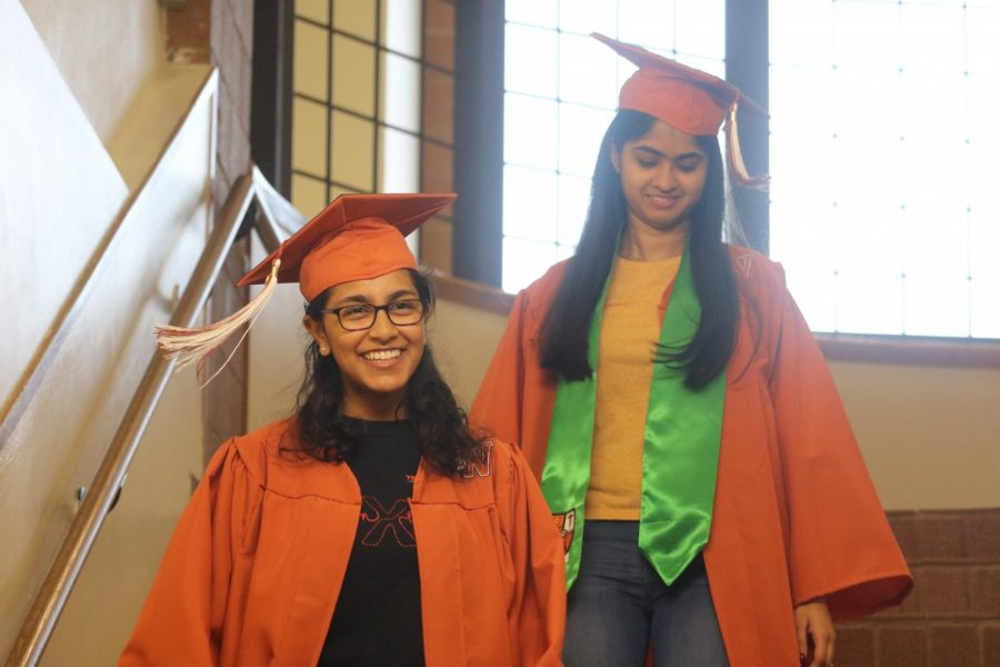 Seniors Sneha Rajendran and Nikitha Majjiga walk down the stairs and are greeted by cheers from the faculty.