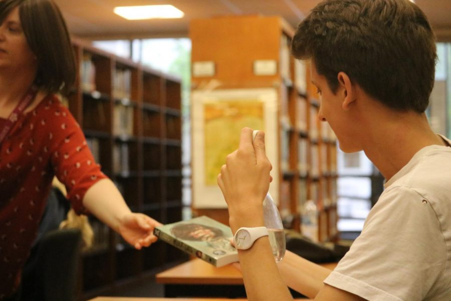 Timothee Peraldi '21 receives a book that he won from the drawing.