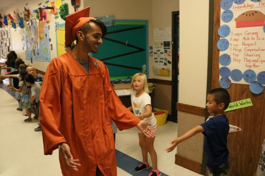 Azaan Moledina '19 looks at a Spicewood student, high-fiving them as he passes.
