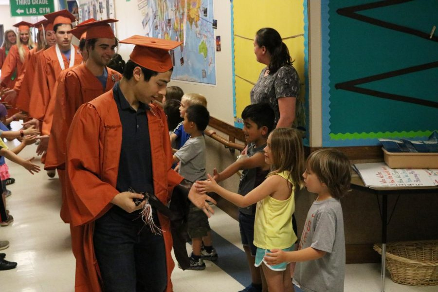 Jason Math '19 high fives a kindergartener as he walks down the hall.
