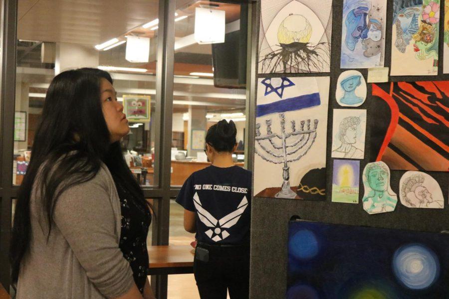 Jenny Tran 20 looks at students art.