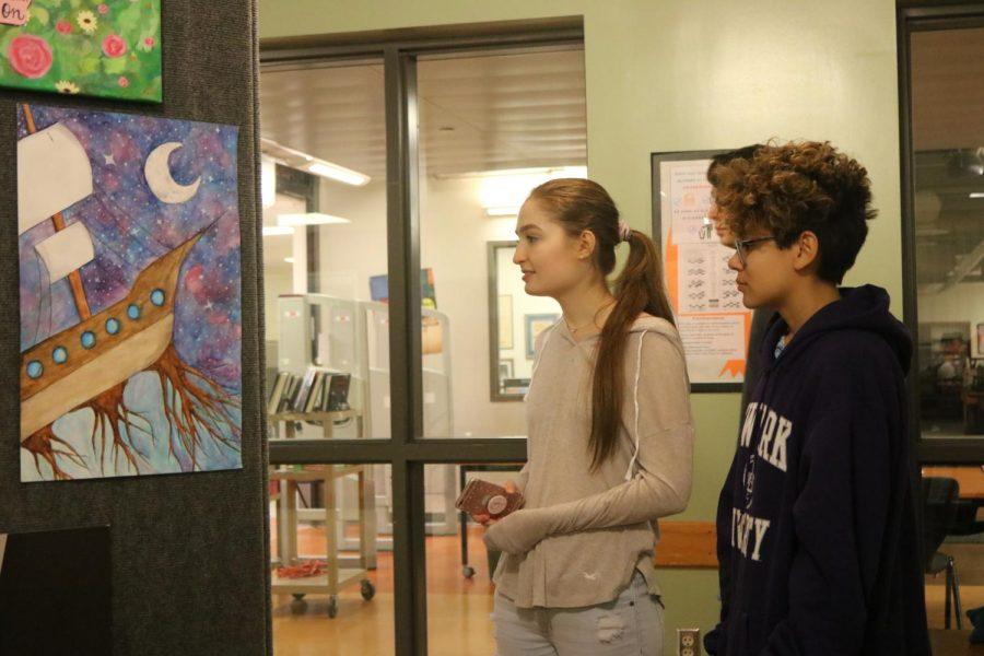 Seniors Haley Talton and Ysavela Ybarra discuss students artworks.