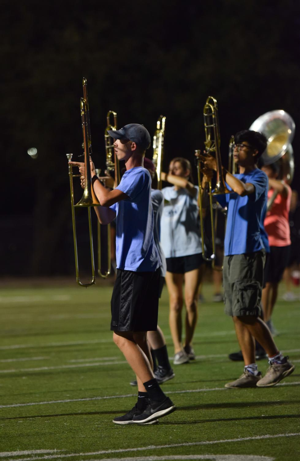 Along+with+other+trombone+players%2C+Hart+Black+%2721+marches+across+the+field+in+formation.