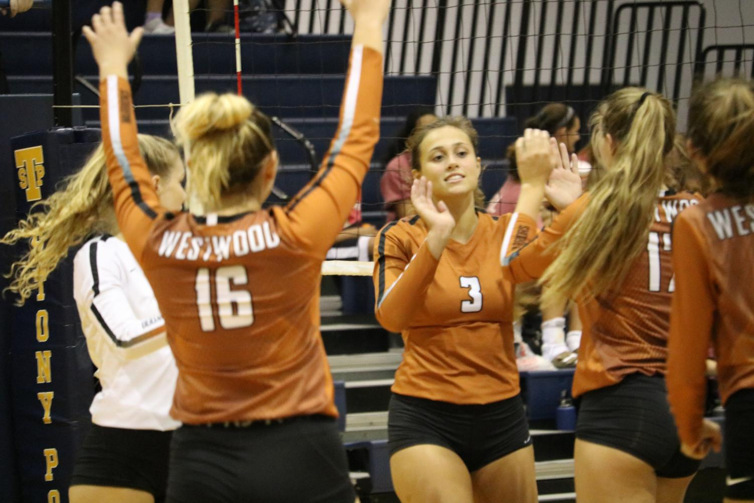 The team celebrates winning their second set of the game. The game ended with the Warriors winning all three sets.