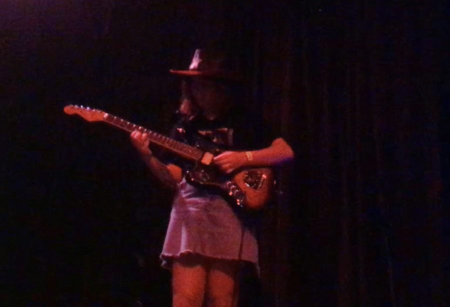 Maggie Geeslin strums her guitar as violet and red lights backdrop her.
