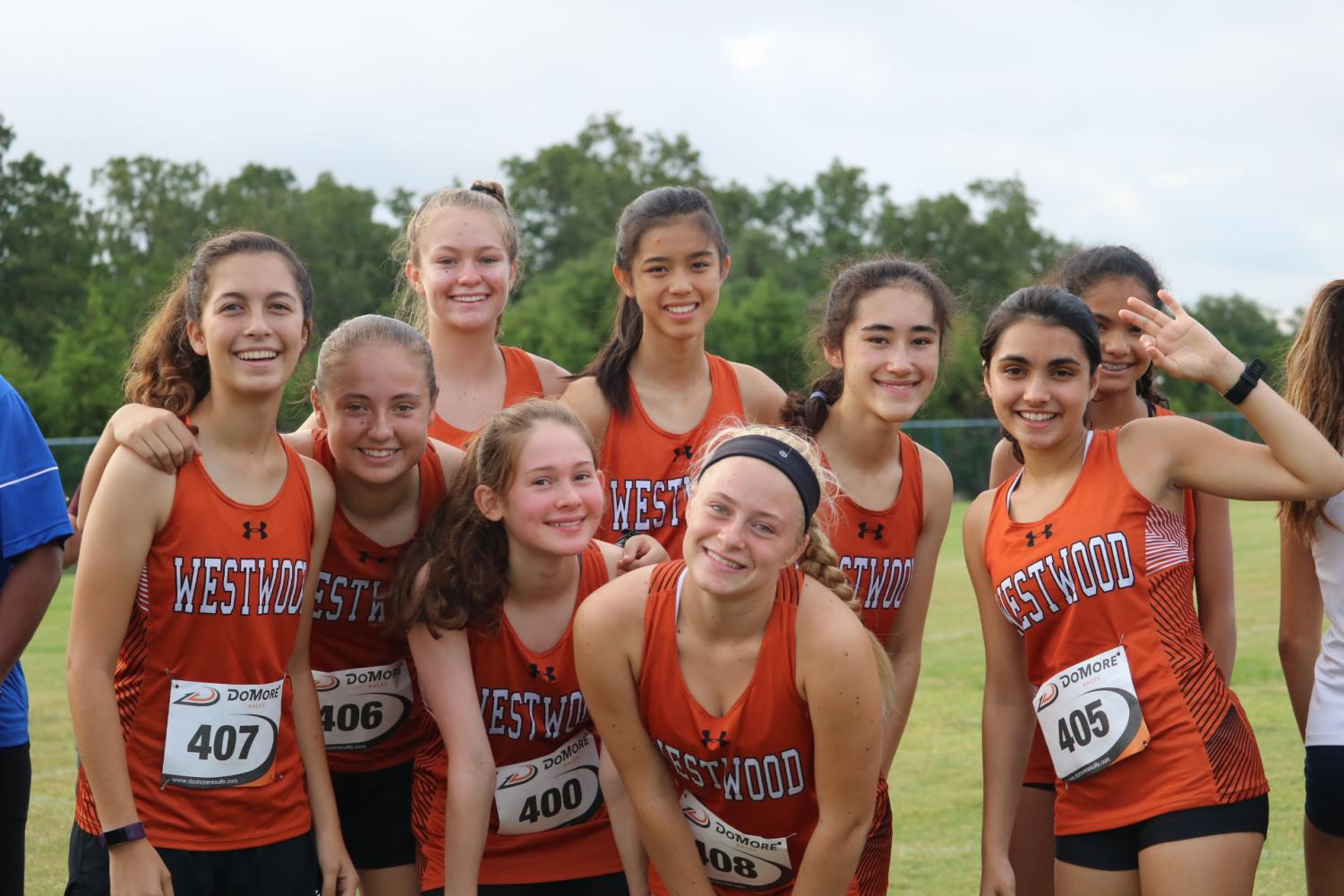 The+varsity+girls+smile+for+a+picture+before+their+race.