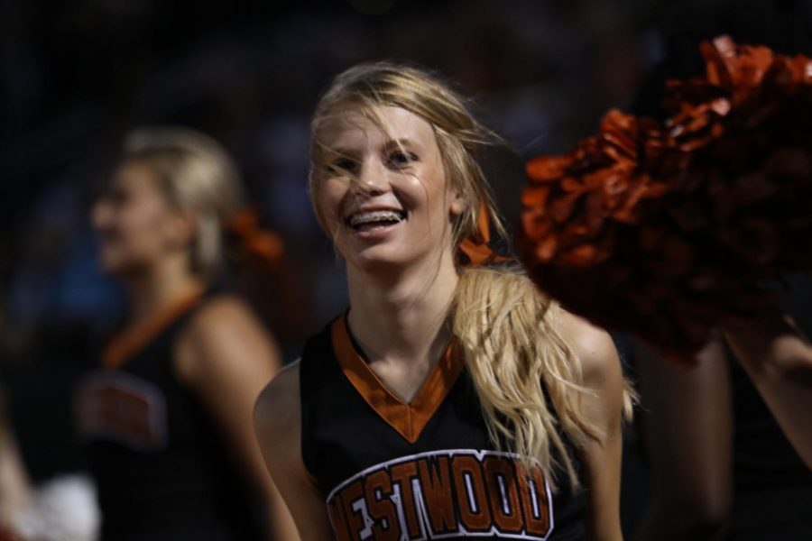 Bailey Trigg 20 smiles and shows her school pride as she cheers for the football team alongside other cheer peers.