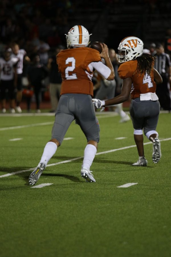 Nate Anderson 21 gets open for a pass, and quarterback RJ Matinez 21 makes a pass to Anderson.
