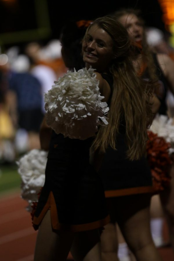 Abby Cook 20 points her pompom at the camera and cheers for her team.