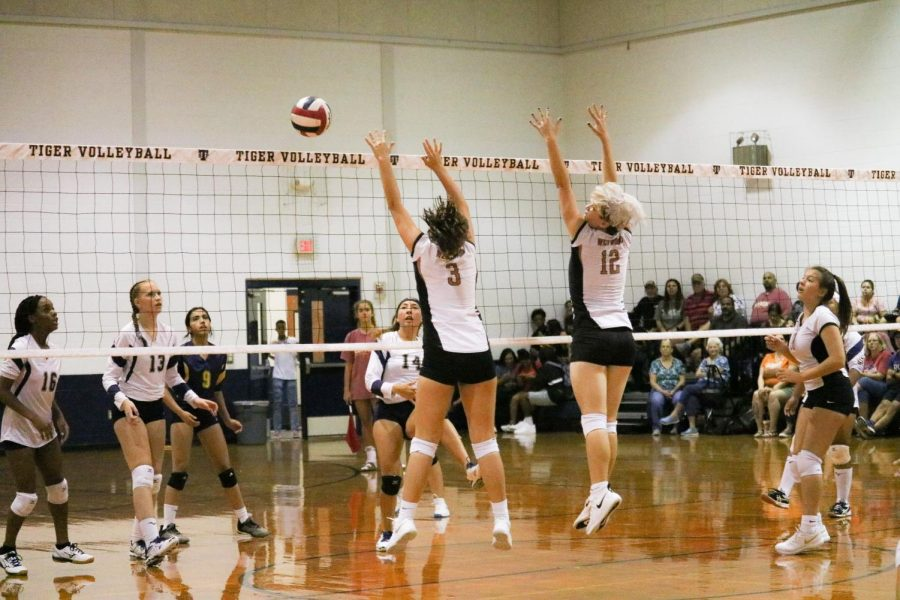 Freshmen Kylie Wardlow and Ella Wood prepare to hit the ball. Wardlow is a middle blocker and Wood is an outside hitter.