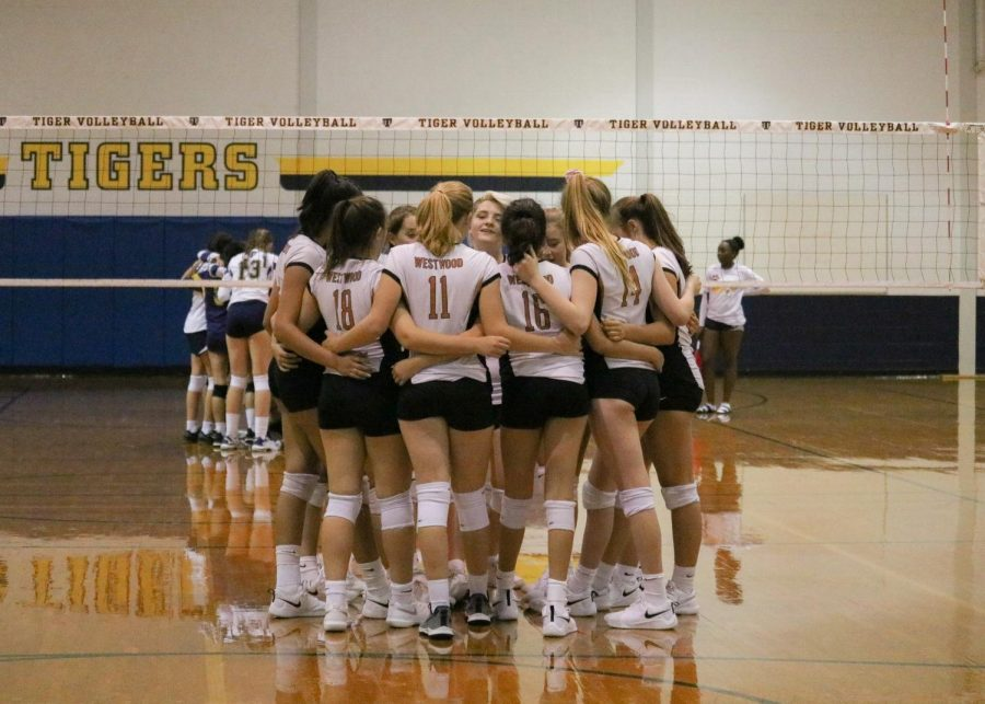 The Freshman Volleyball team huddling together before their first set. Despite their best efforts, they lose the first set.