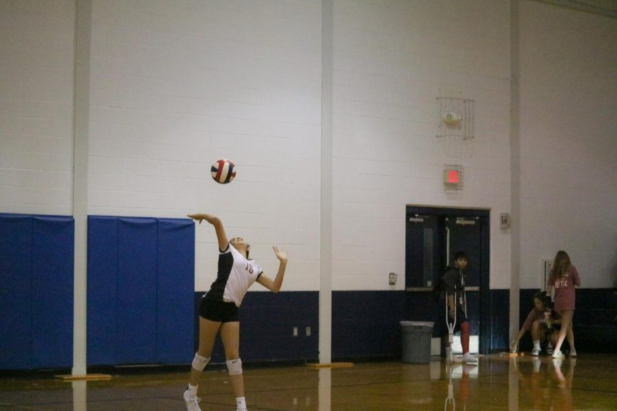 Eliana Oquendo '23 serves the ball. Oquendo is a defensive specialist on the volleyball team.
