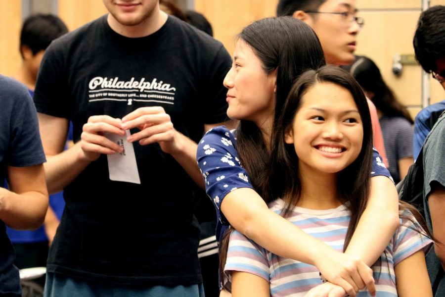 Watching fellow musicians open their squad letters, violinist and orchestra officer Anna Beatty '22 is hugged from behind by a friend.
