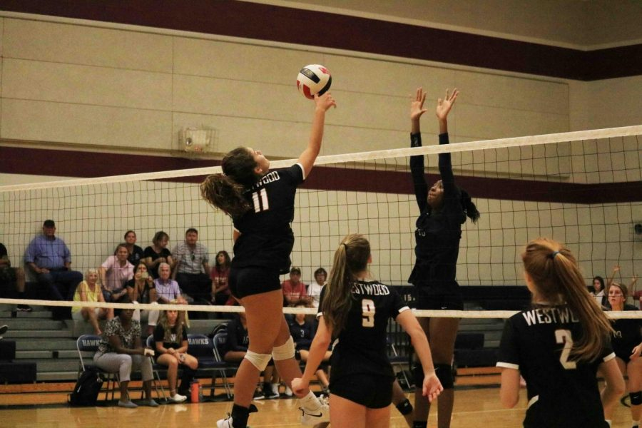 Allie Shepherd '23 spikes the ball over the net. Shepherd is a middle blocker on the team.