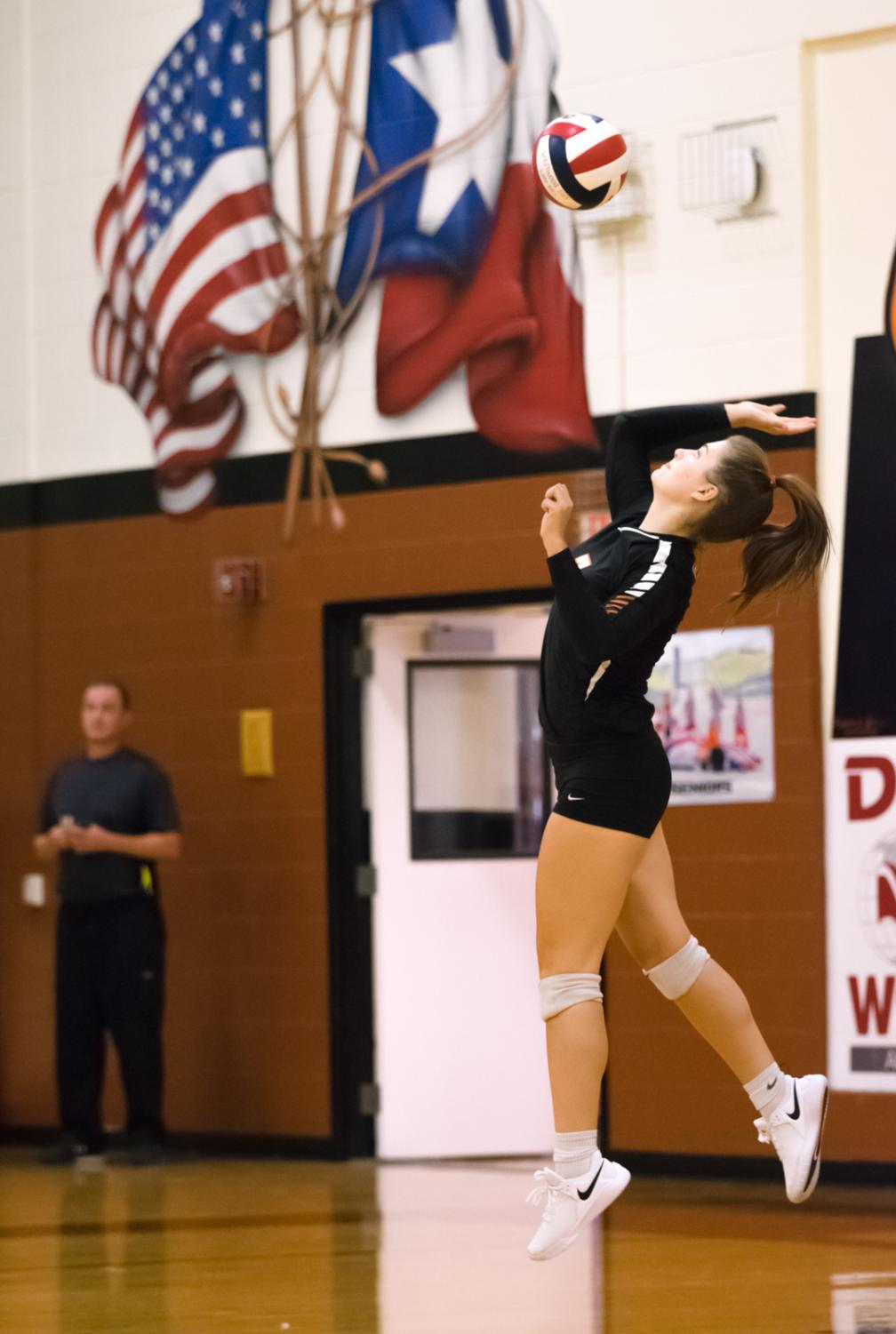 Kenna+Williams+%2722+jumps+to+serve+the+ball.+Williams%27+serve+resulted+in+a+point+for+the+Warriors+towards+the+end+of+the+second+set.