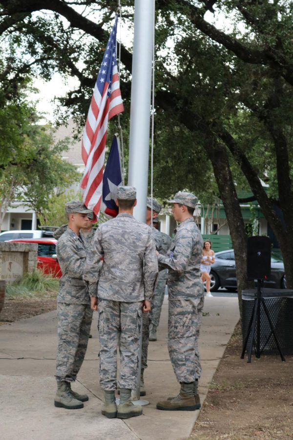 Owen Darden '20 lowers the flags with the help of three other cadets. JROTC takes the flags down every day after school, though most days only three cadets in total do the job.