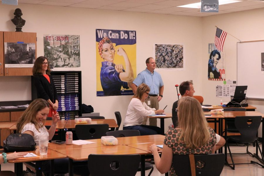 Mr. Carl Bradley explains his curriculum to parents. The parents follow along and take notes on his presentation.