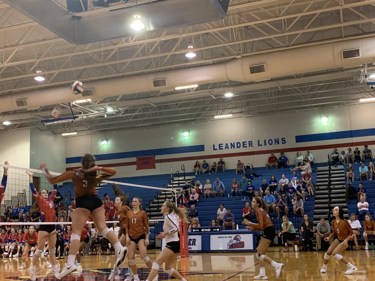 Abby+Gregorczyk+%2721+gets+ready+to+spike+the+ball+over+the+net.++Meanwhile%2C+the+Leander+Lions+are+up+against+the+net%2C+ready+to+hit+the+ball+if+she+gets+it+over.