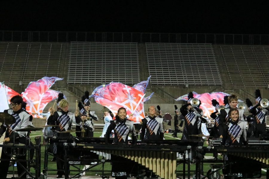 The percussion section plays their part as the colorguards wave their flags behind them. Some of the colorguards had blue flags with snowflakes on them.