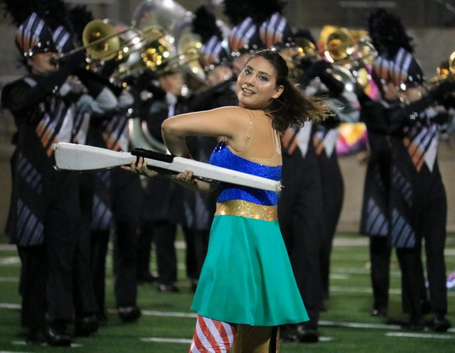 Oriana Yates '20 performs a colorguard routine with a rifle. Rifles are Yates' favorite part of colorguard.