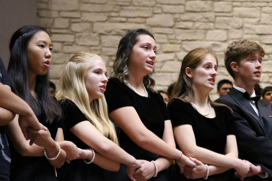 Seniors Violet Rogers, Elsa Hughes, Sarah Sherwood, and Rachel Rusch hold hands while singing 'The Lord Bless You and Keep You'. This song is sung at the end of every concert, and the seniors stand in front while performing this song.