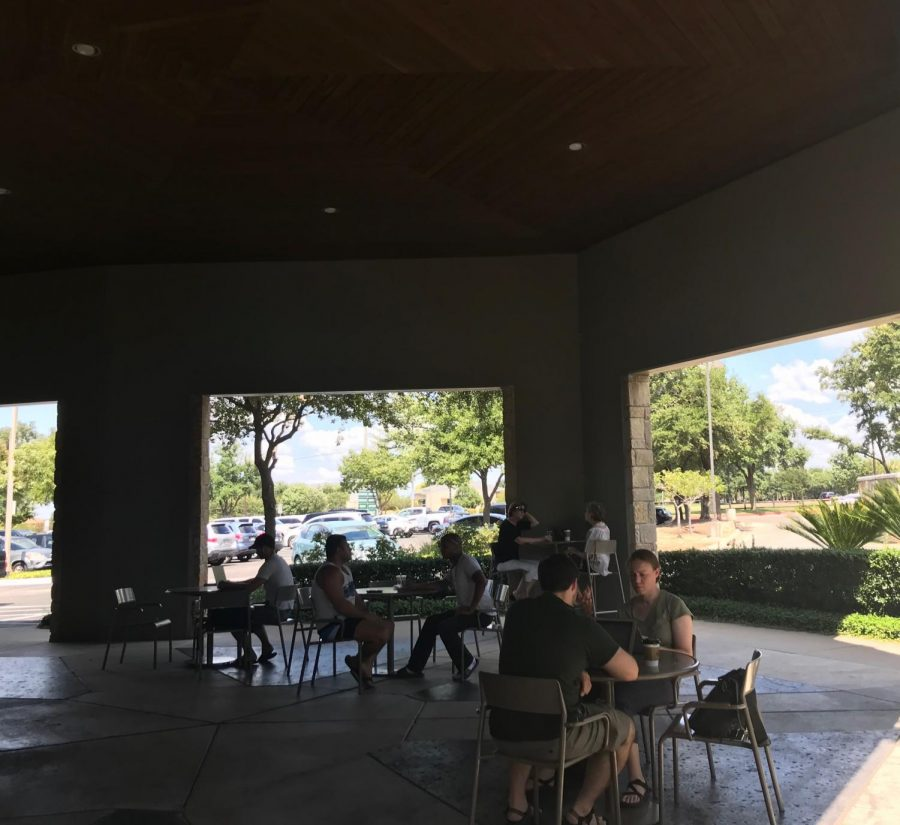 Immediately outside the entrance, there is a small seating area where customers can enjoy their drinks in an outdoor environment.