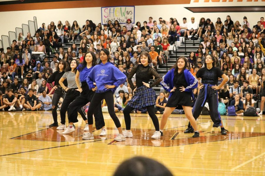The K-Pop club energetically dances at the pep rally.